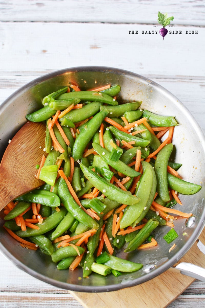 sauteed sugar snap peas in skillet with garlic and matchstick carrots being stirred by a wooden spoon