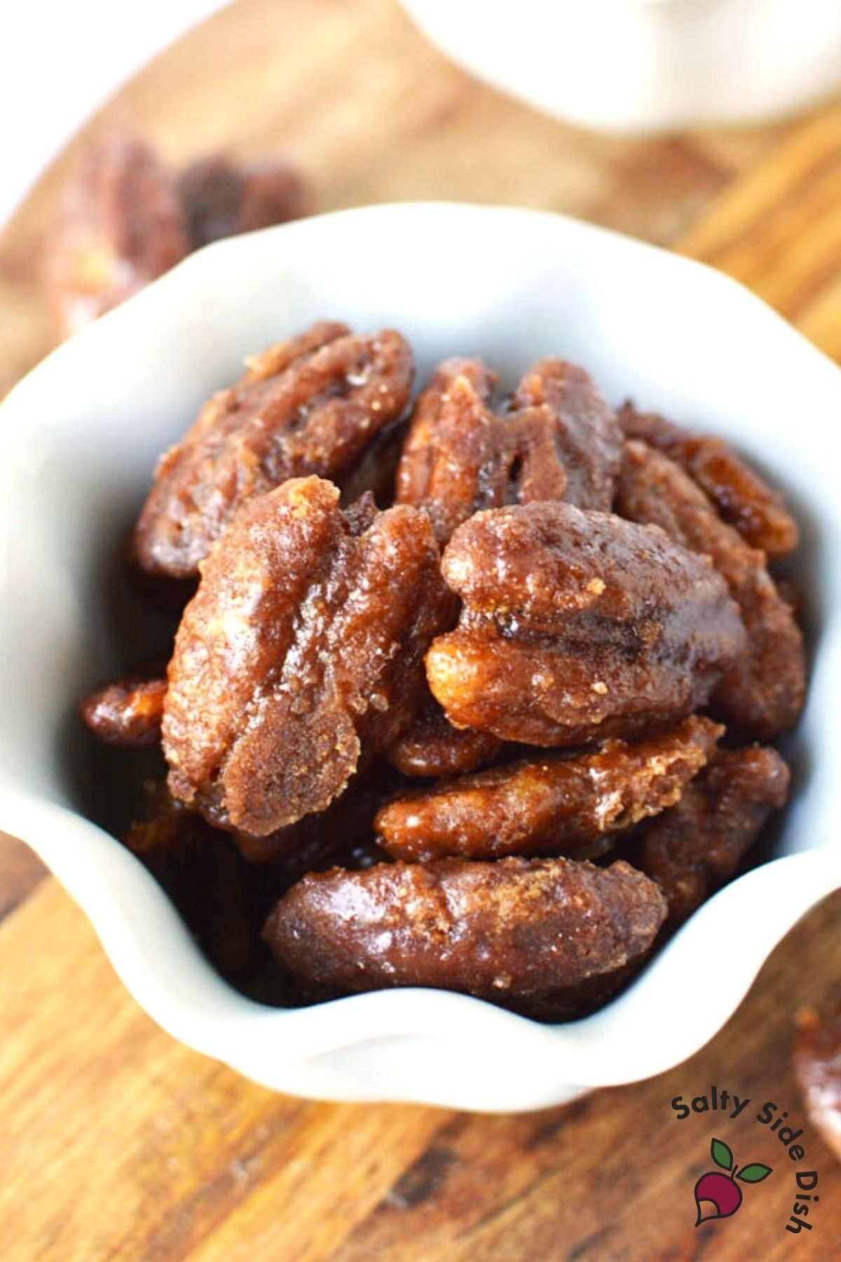 white bowl of candied pecans sitting on a wooden table