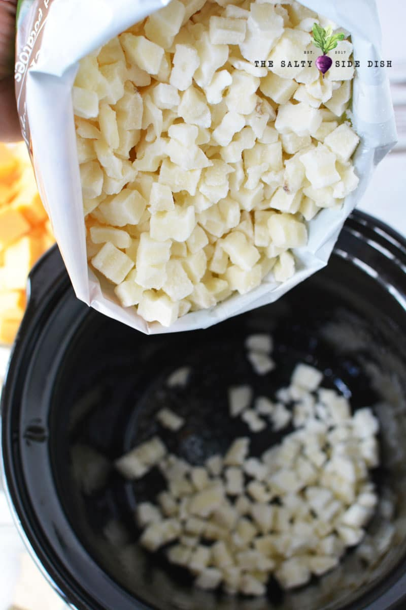 dumping frozen potatoes in the slow cooker ready to make a side dish