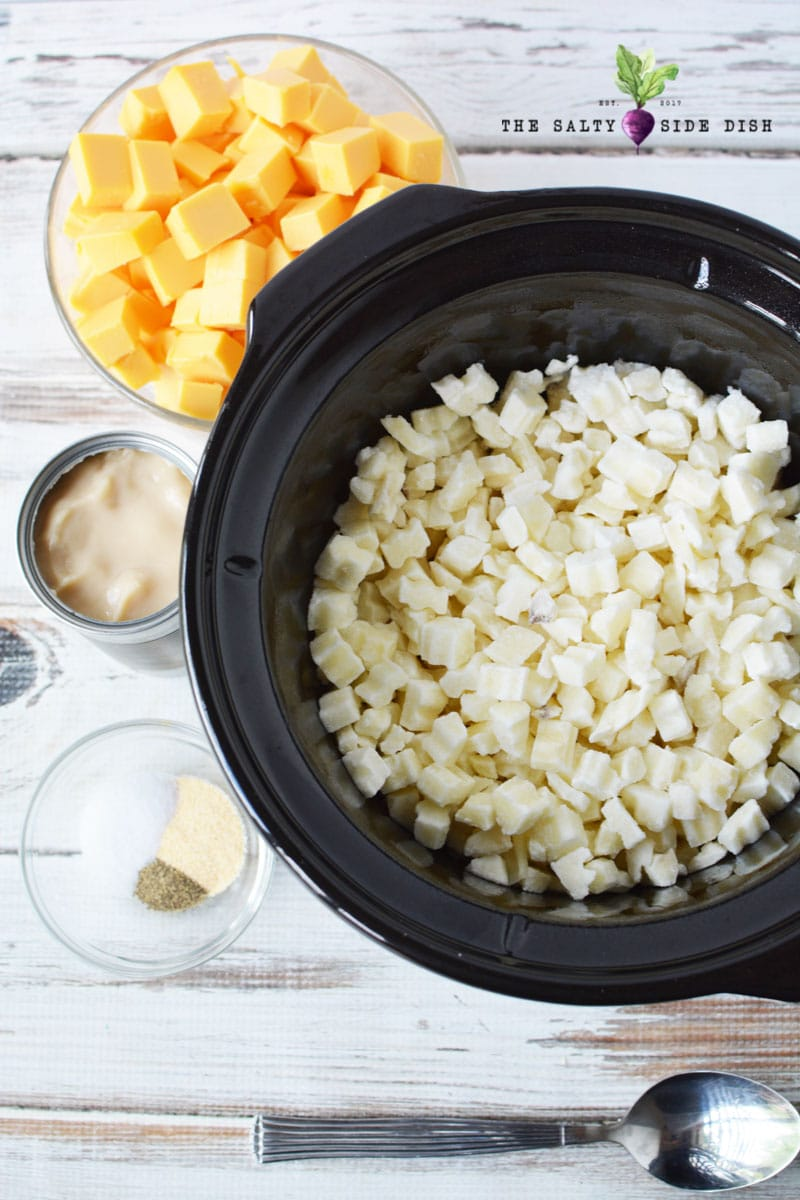 cheesy potatoes ready to be made in a slow cooker with ingredients on the counter