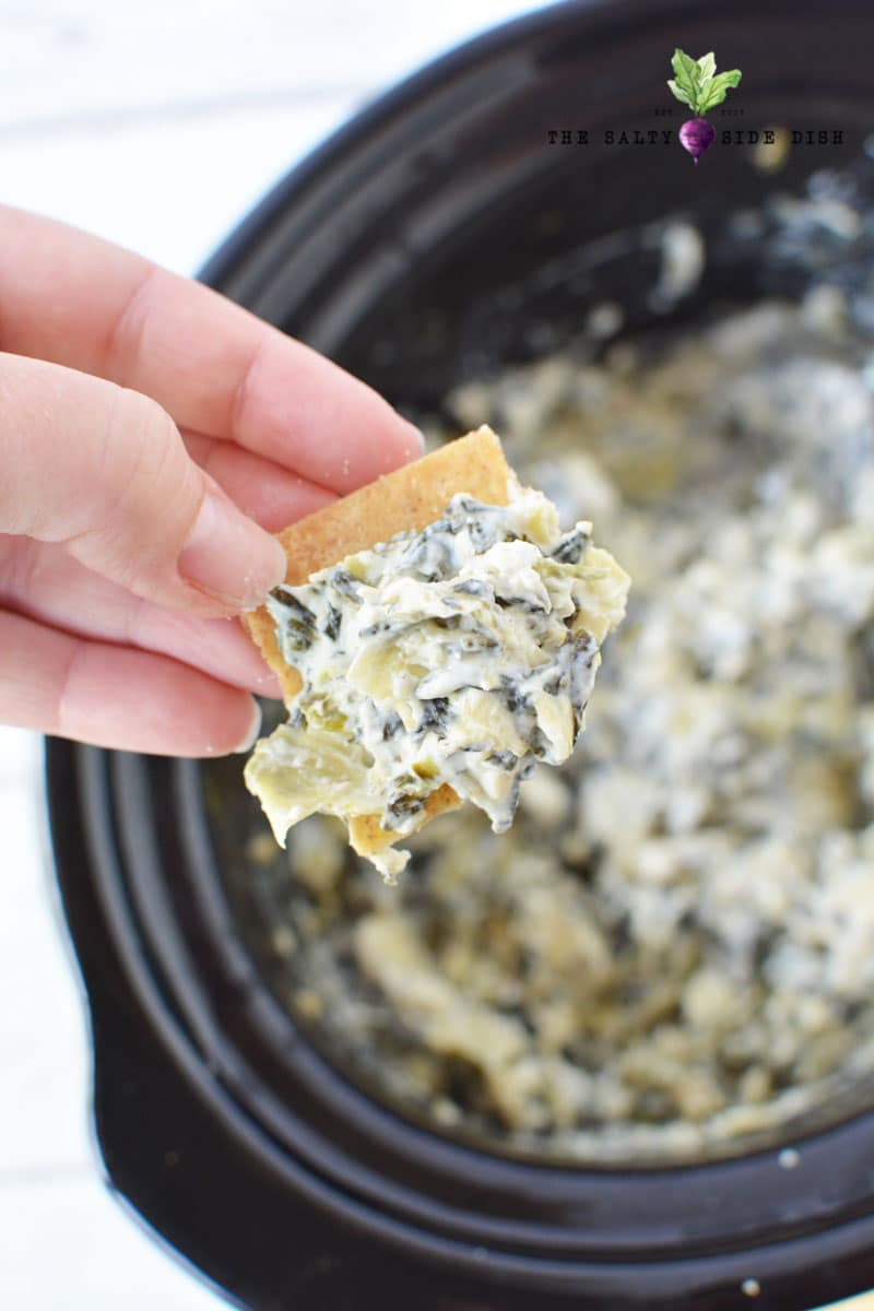 chip dipped in Spinach Artichoke Dip in the crock pot