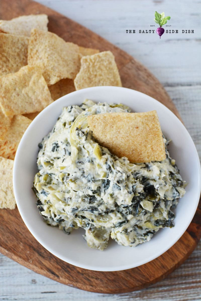 bowl of Spinach Artichoke Dip on plate with pita chips
