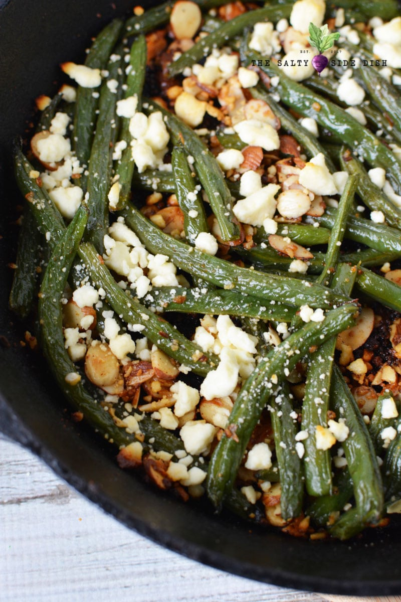 Green Beans Almondine with garlic and feta cheese in a cast iron pan and ready to serve for dinner