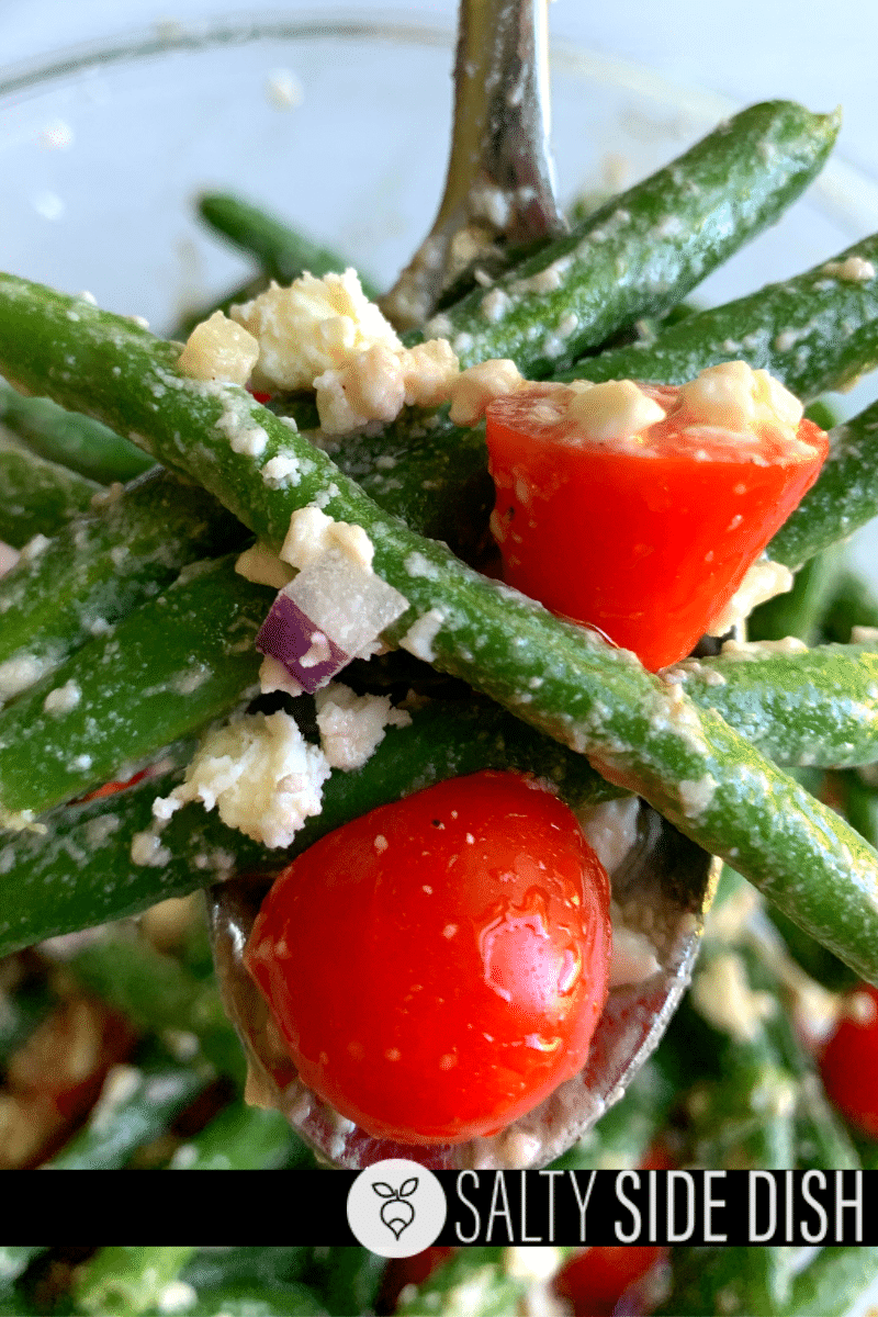 Green beans with red onion, feta, and tomatoes on a serving spoon