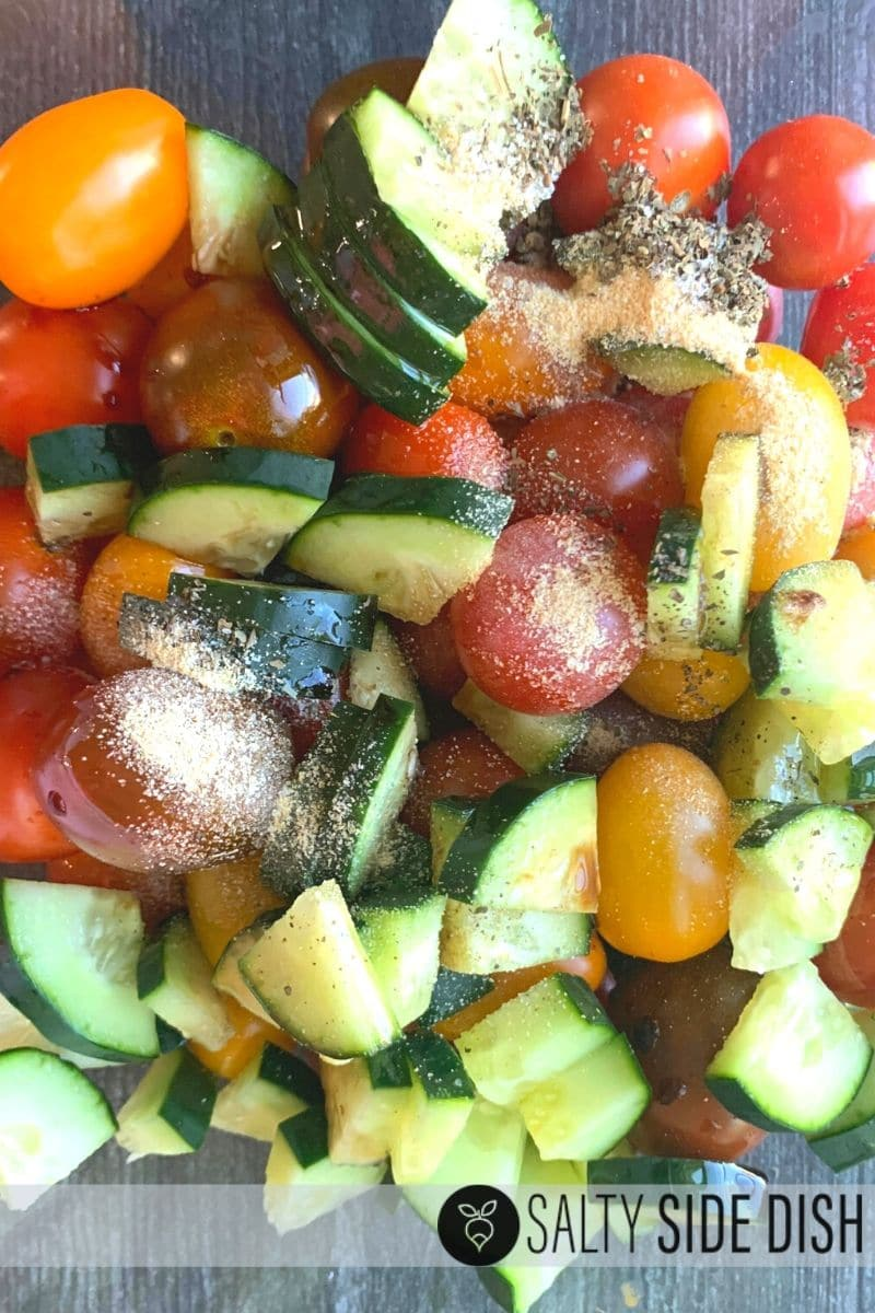 seasonings like garlic dumped over cut up cucumbers and tomatoes in a bowl