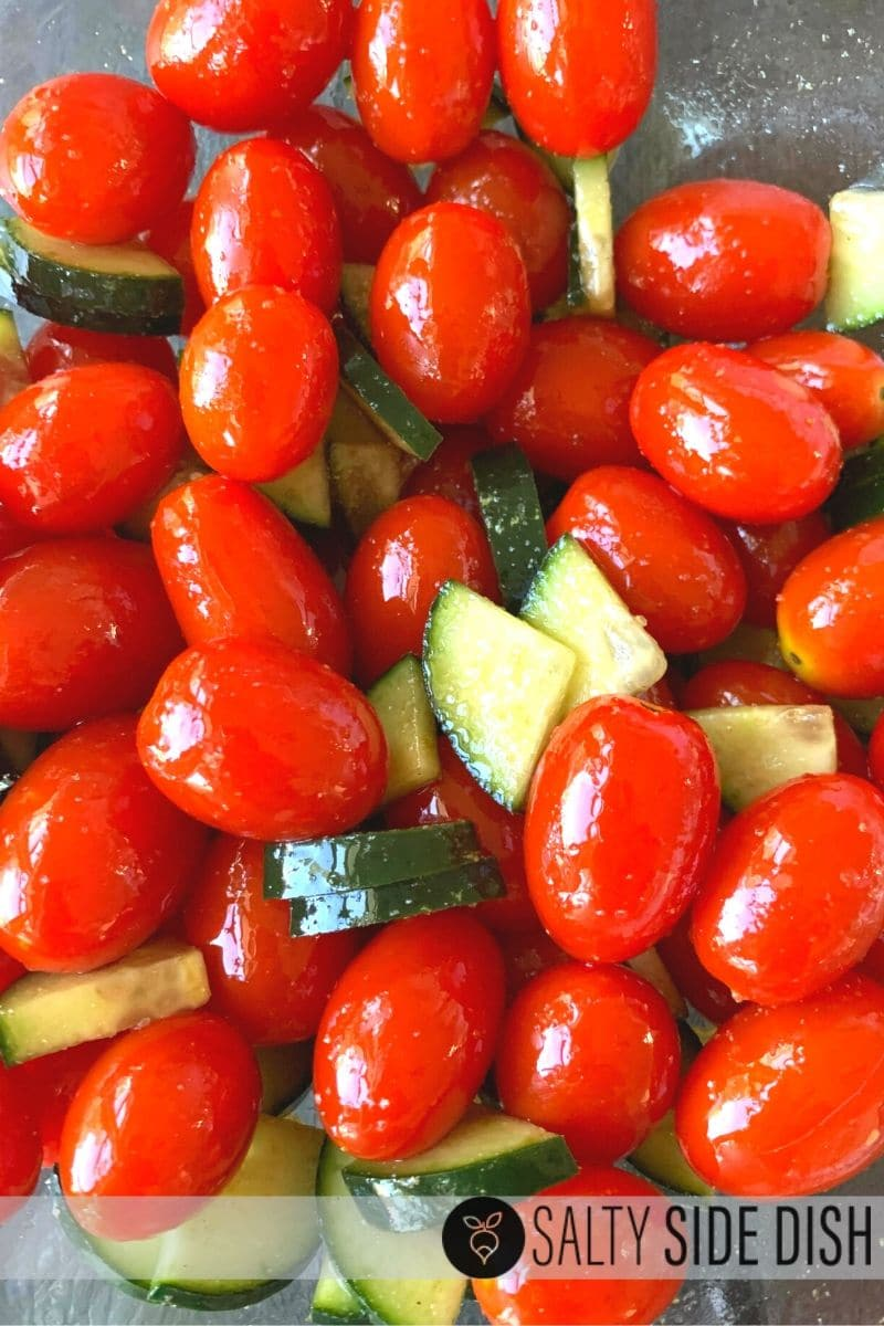 Cherry tomatoes with quartered cucumbers cut up and covered in seasonings and oil in a bowl to make a Christmas Salad