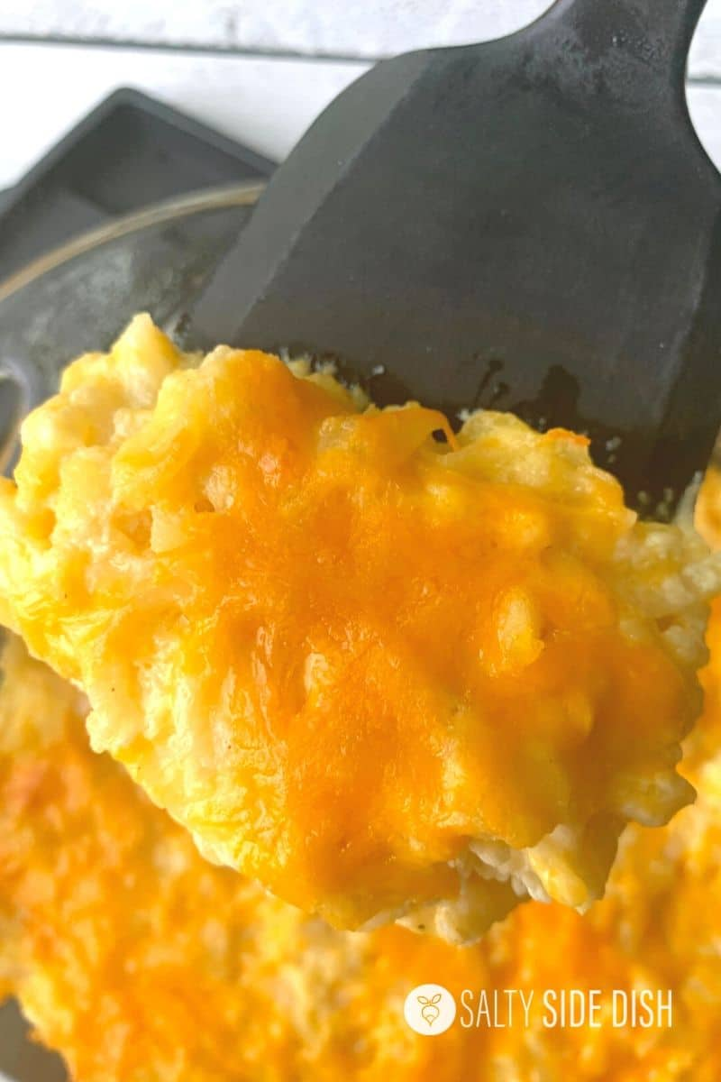 cheesy hashbrown casserole baked in oven and on a spatula