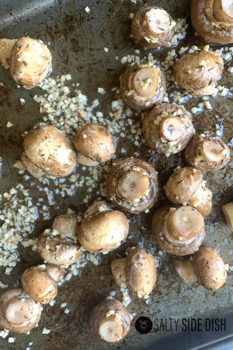 pan roasted white button mushrooms laying on sheet pan in garlic