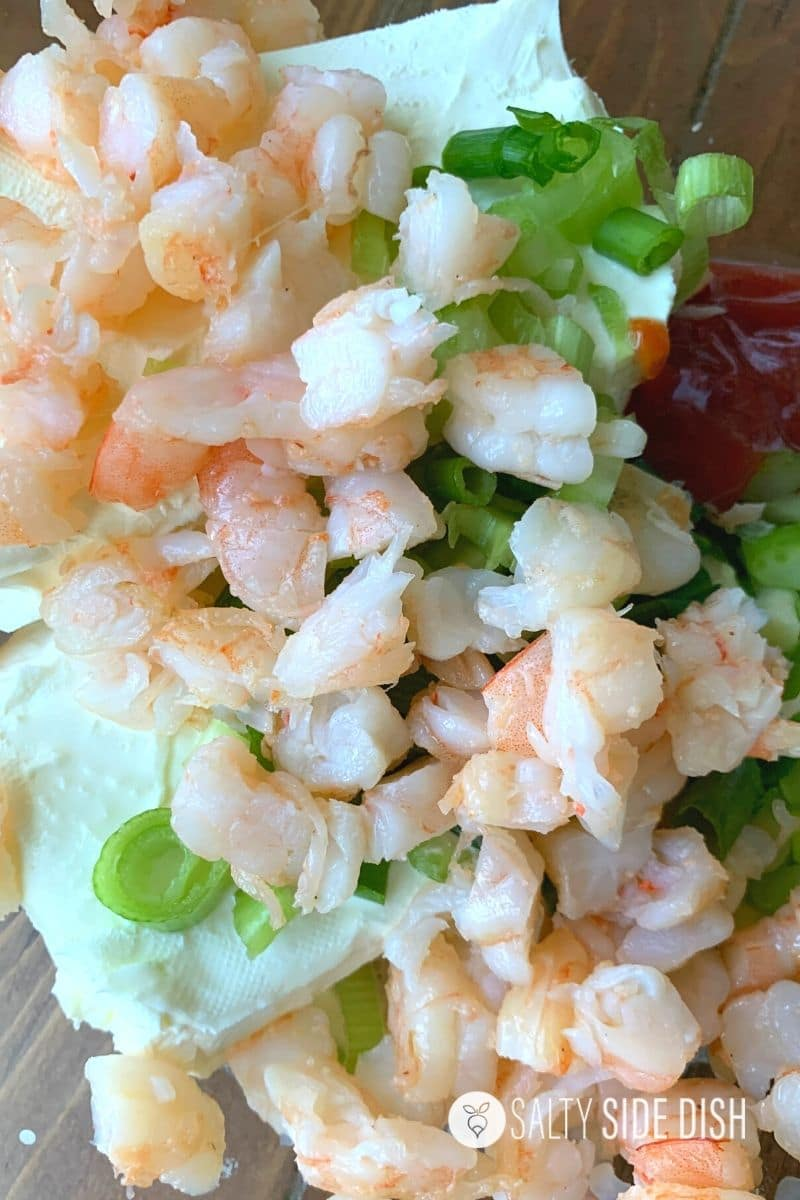 fresh shrimp cut up and added with onions, spices and cream cheese in a bowl