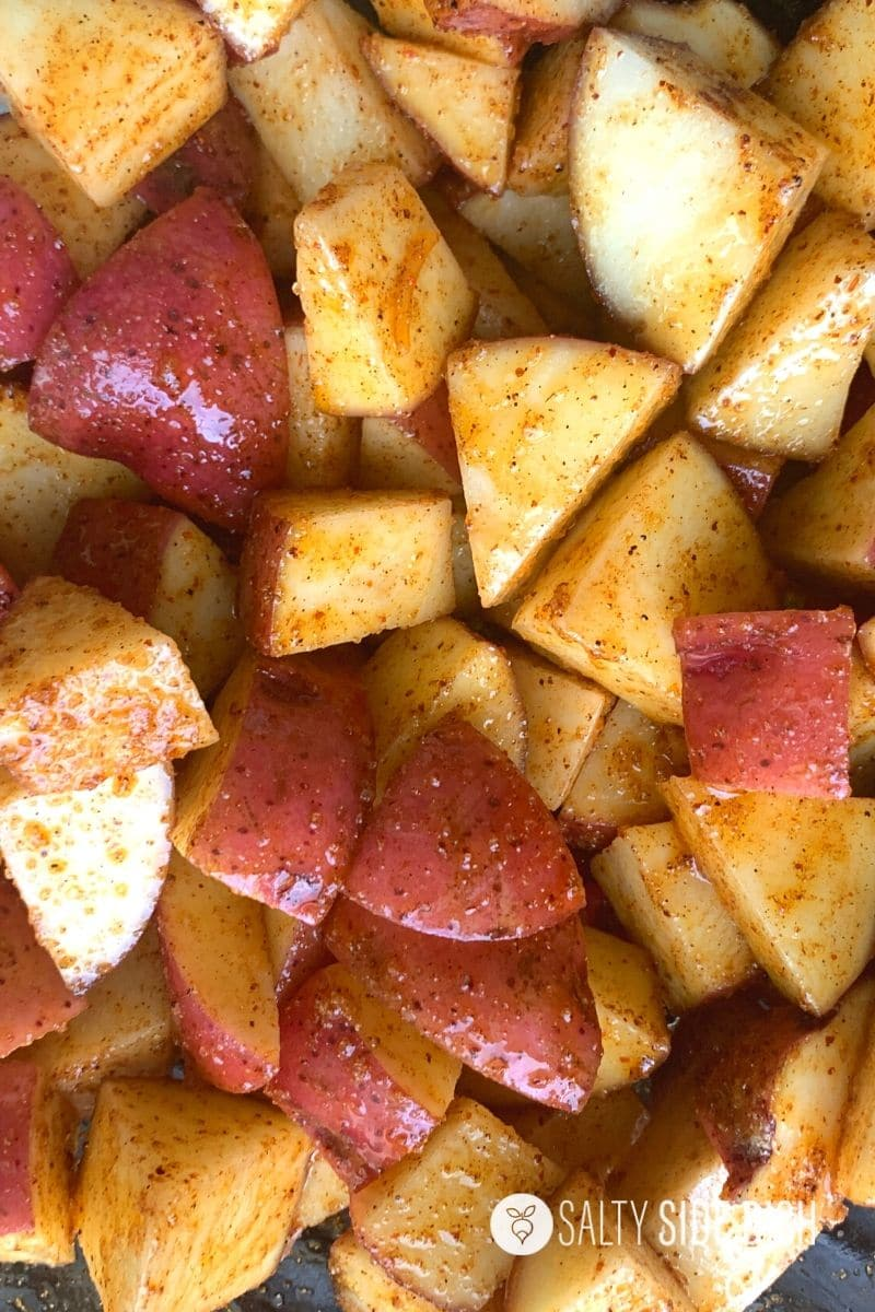 red potatoes in bowl with oil and chili powder on them