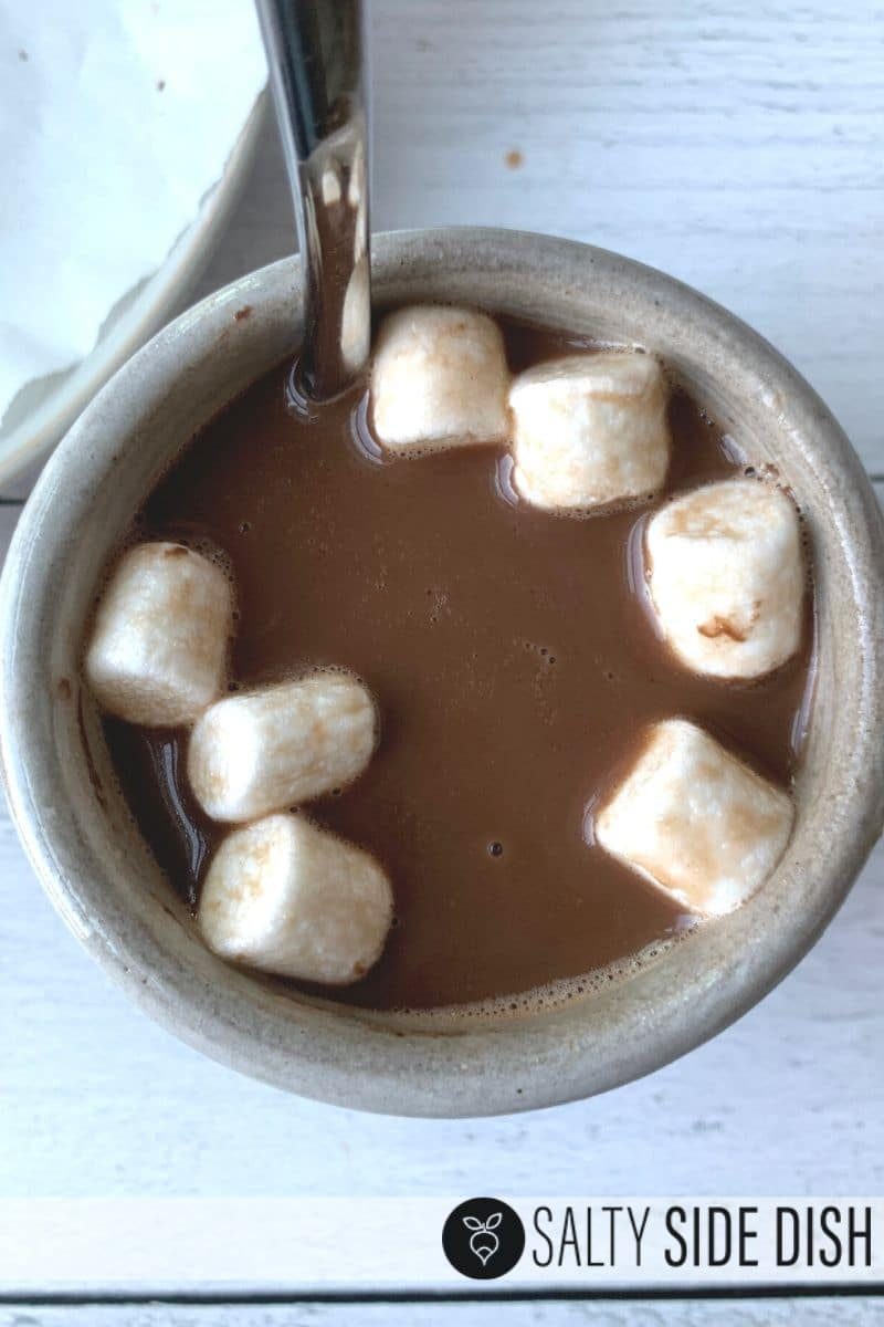 marshmallows pop out of chocolate balls in coffee cup