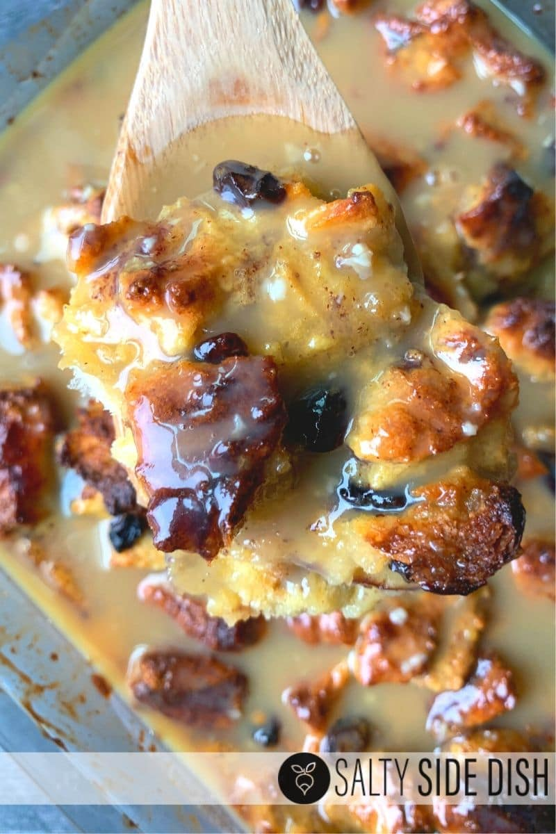 Apple Cinnamon Bread Pudding with Caramel Custard Glaze sauce on a wooden spoon