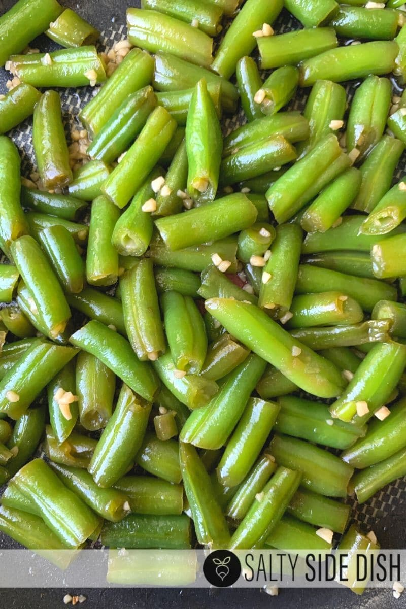 green beans in a wok with fresh minced garlic