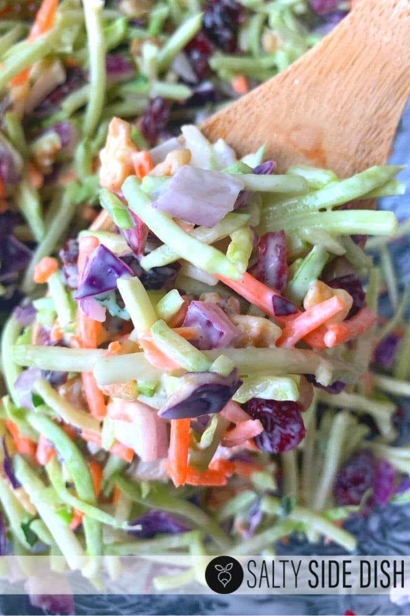 Broccoli Slaw Salad with Creamy Dressing being served out of a bowl on a wooden spoon