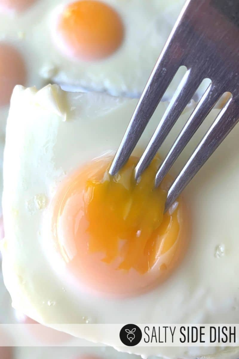 Sheet pan eggs with fork breaking open soft yolk