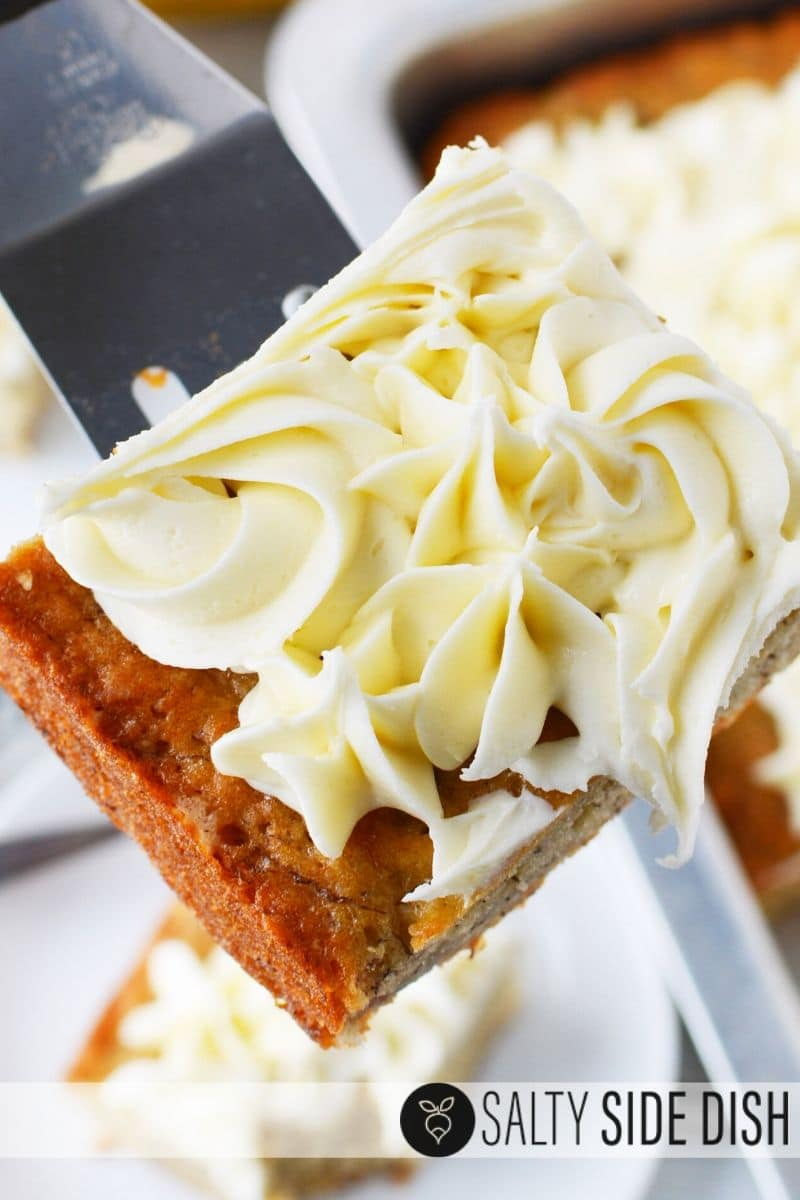 banana bread cake with cream cheese frosting on a spatula ready to serve as dessert