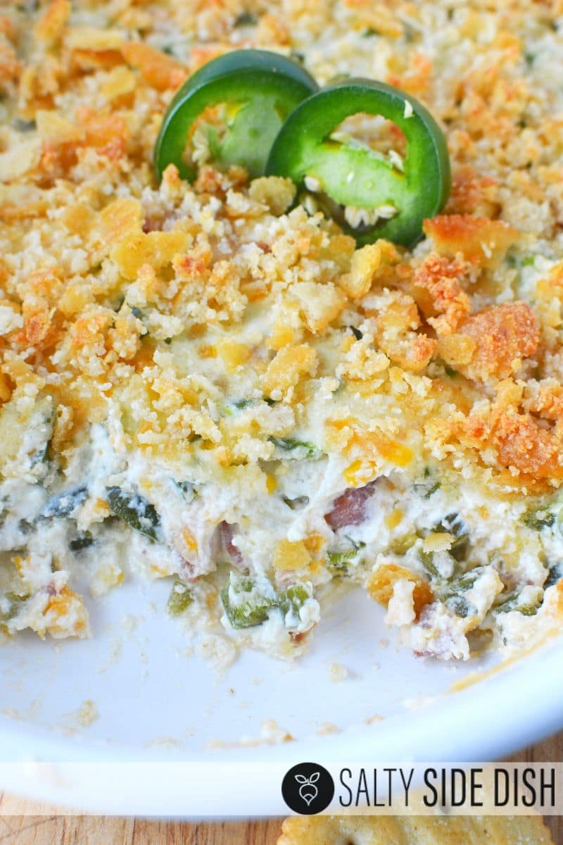 hot and creamy jalapeno popper dip in a casserole dish and two cut jalapenos on top