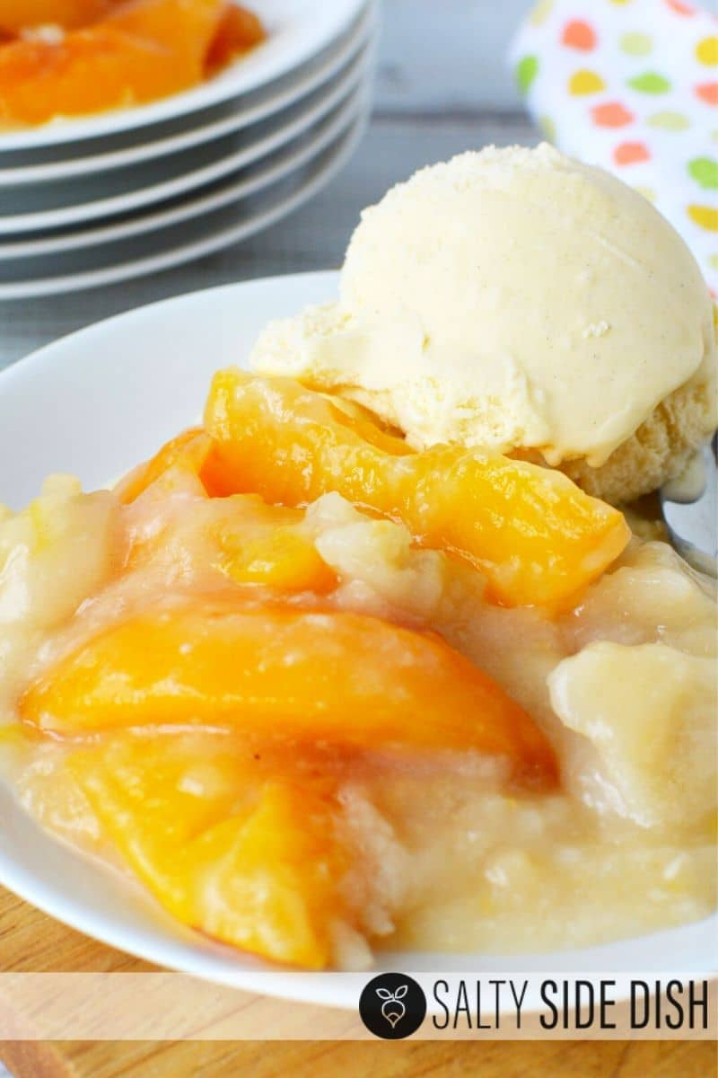 Peach Cobbler Dump Cake on a plate with creamy bisquick and vanilla ice cream