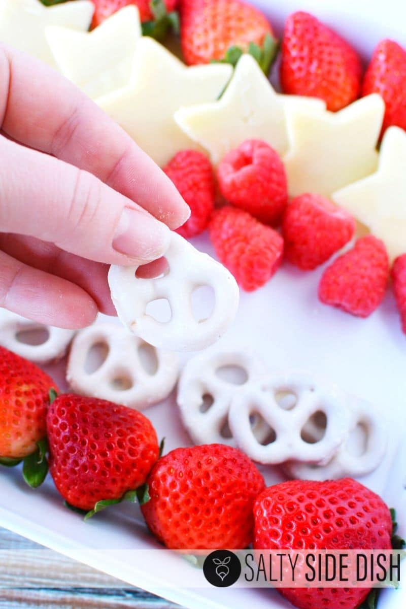 add sweet pretzels to your tray for a sweet treat with hand holding white chocolate covered pretzel on tray