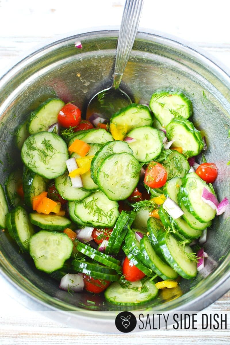 sliced Cucumber Salad with Apple Cider Vinegar with fresh dill and oil vinaigrette mixing up to a side salad