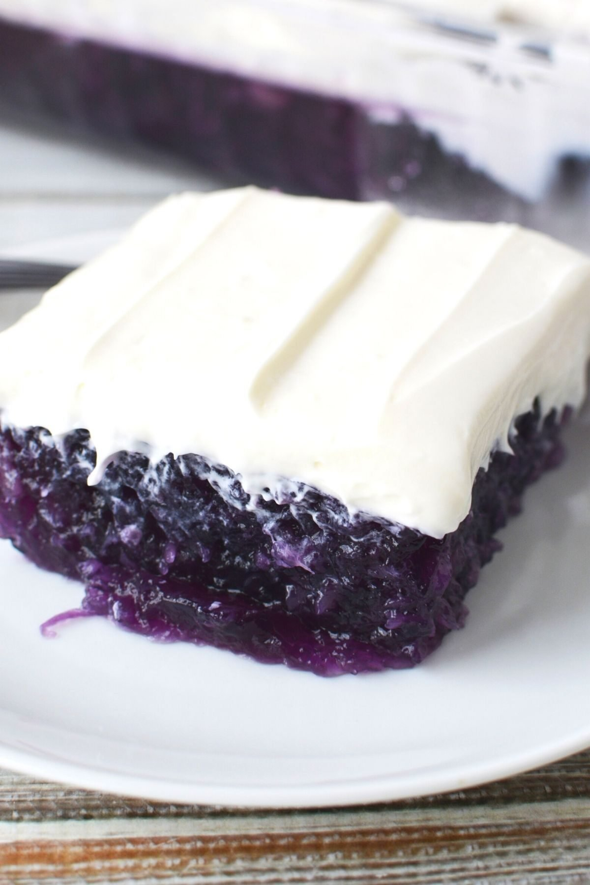 square of blueberry jello salad with cream cheese topping on a white plate.