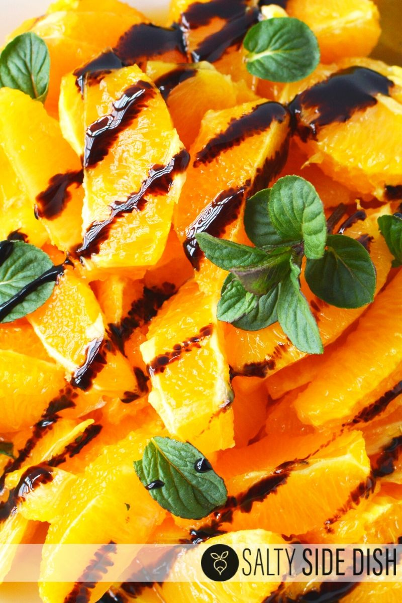 Oranges cut up on a plate with balsamic glaze and fresh mint