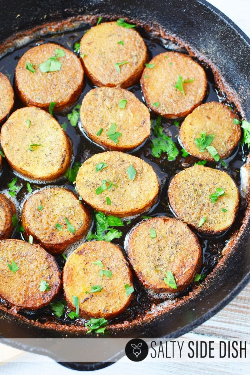 Melting potato recipe sitting in cast iron pan with fresh herbs sprinkled on top