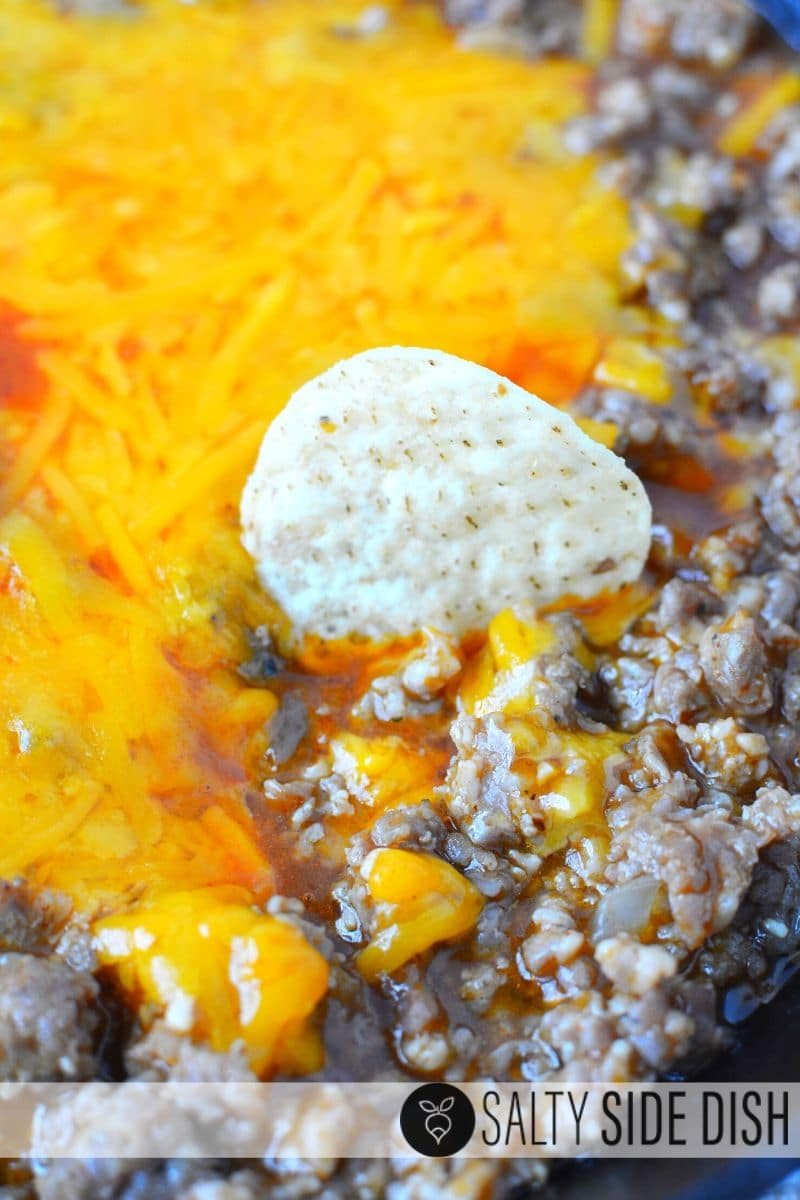 Sausage Enchilada Dip with melted cheddar cheese and a chip sitting in the appetizer dip