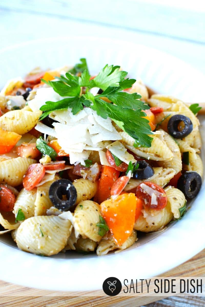 Antipasto Pasta Salad in a bowl with fresh herbs and shaved cheeses
