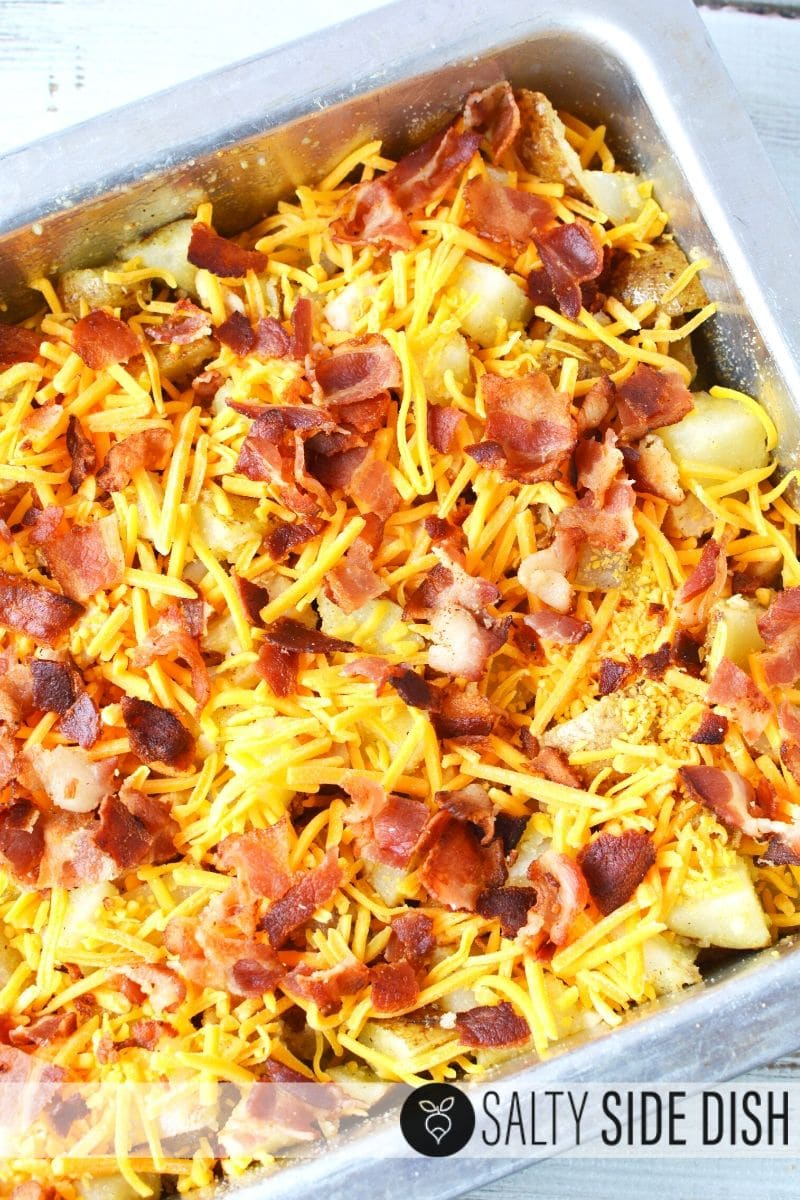 loaded cheddar cheese, cooked bacon, chicken and potatoes sitting in casserole dish
