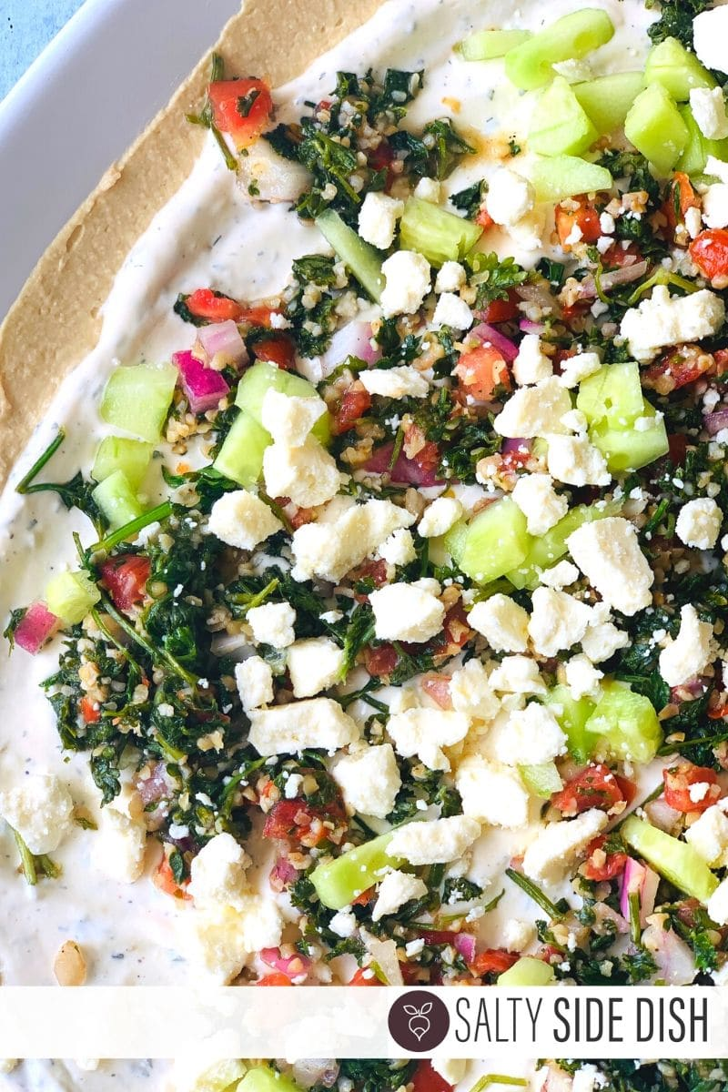 Greek Dip layered with cheese, cucumbers, tabouli on a platter