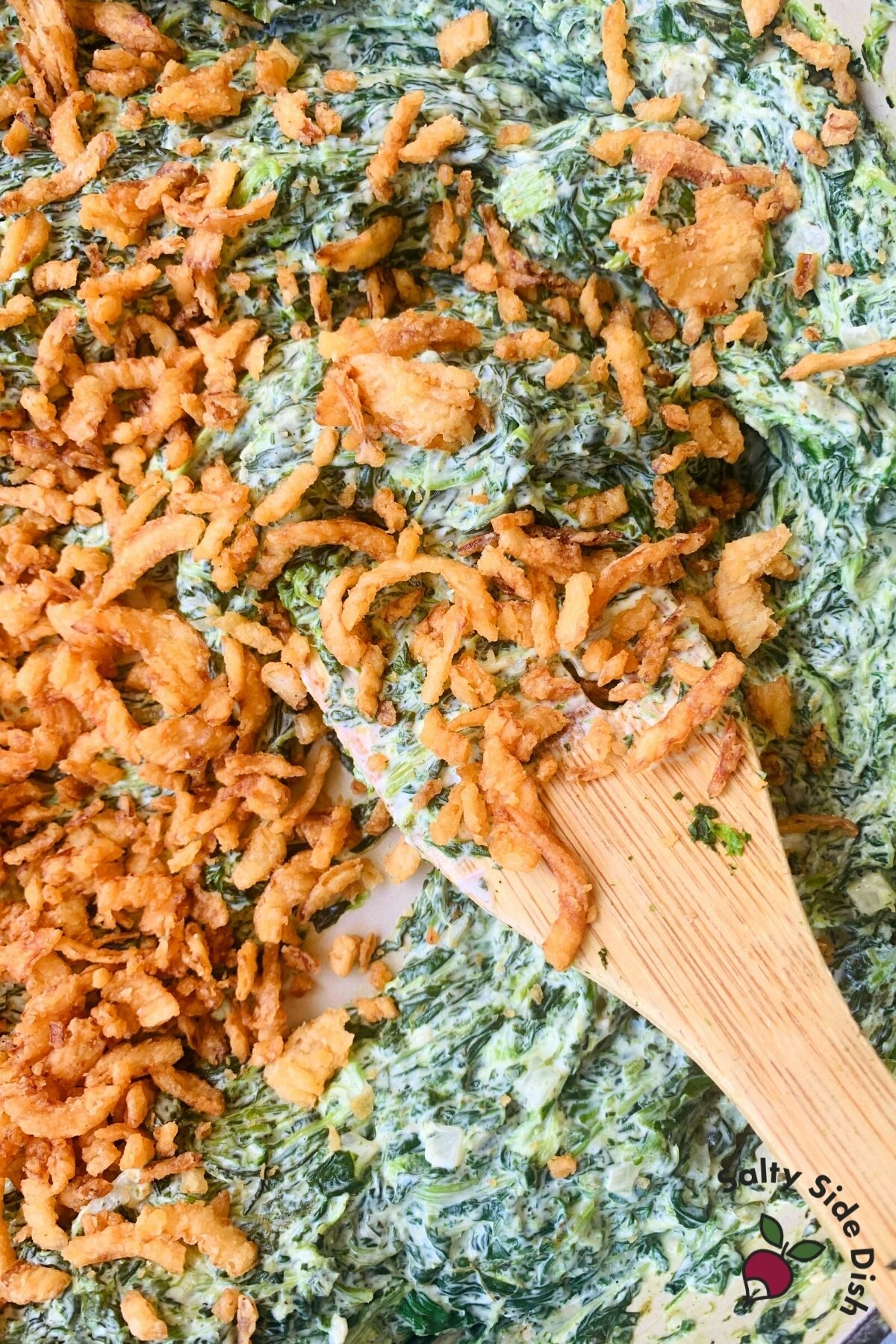 pan with wooden spoon stirring creamed spinach with a lot of French's crunchy fried onions on top