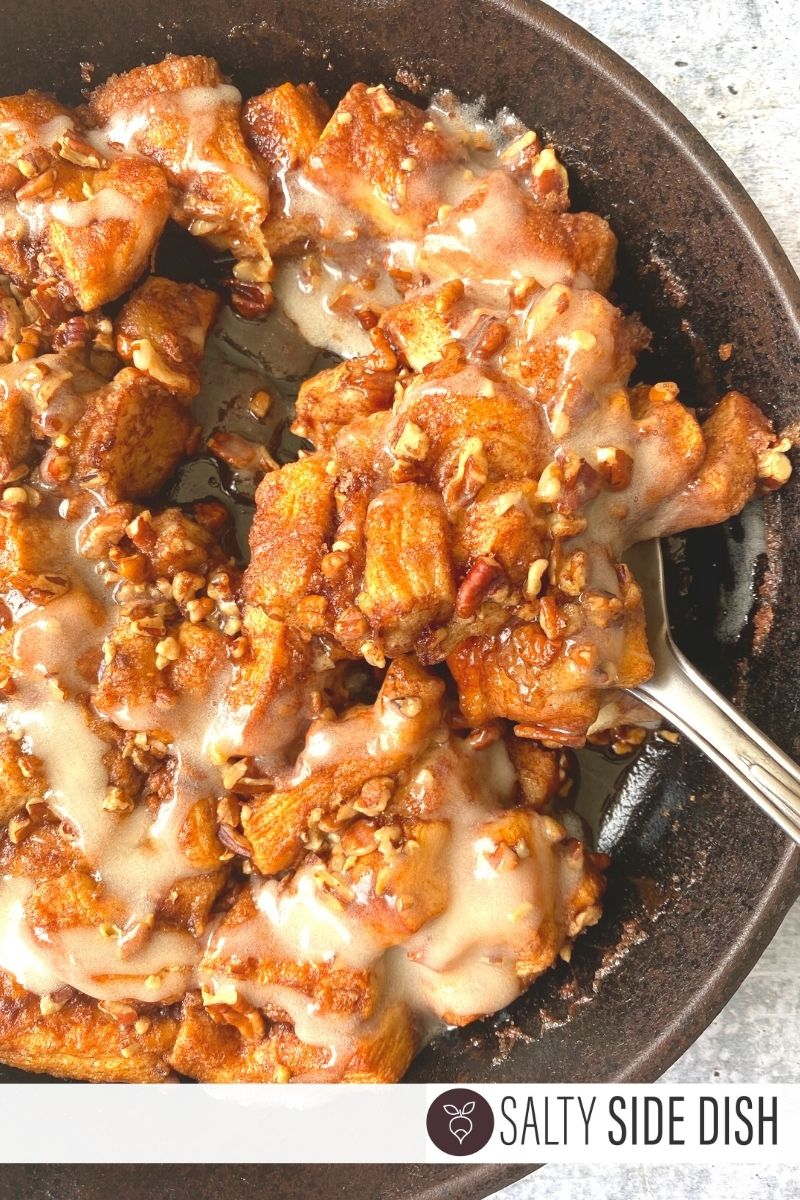 scoop out cinnamon rolls in a cast iron pan ready to serve in a spoon