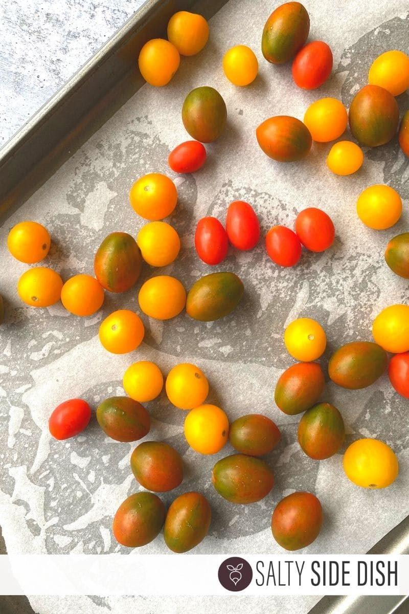 cherry tomatoes poured onto a sheet pan covered in parchment paper