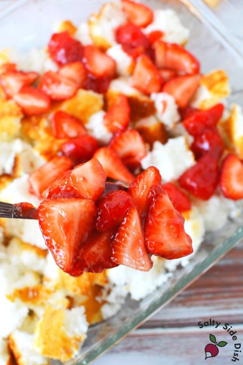 scoop strawberries into layered angel food cake