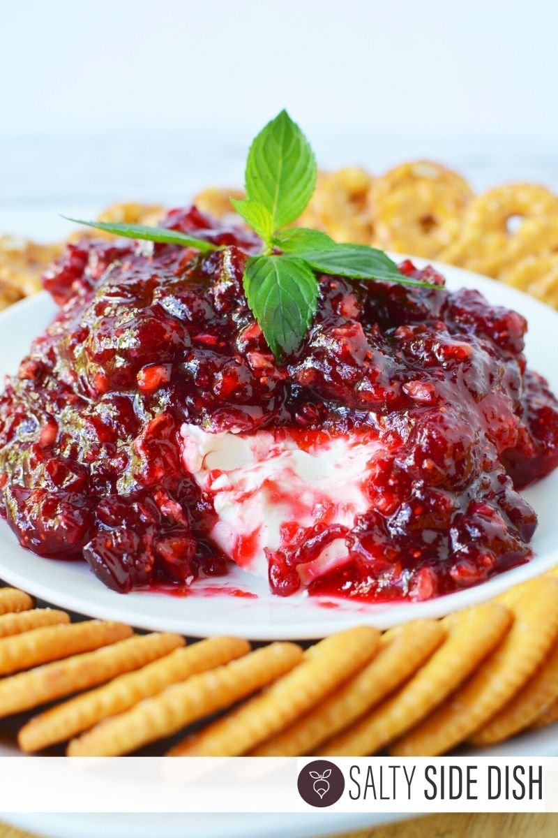 cranberry cream cheese dip with chunk out of it and mint on top