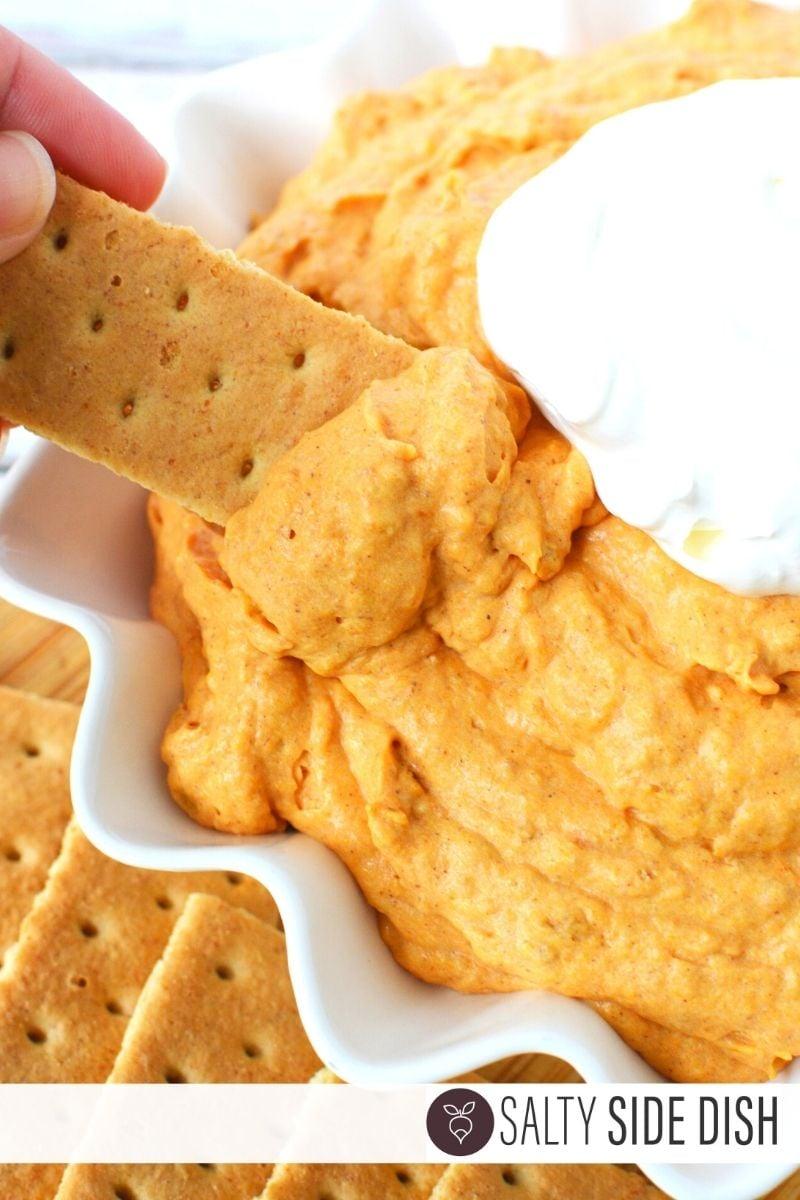 Dipping a graham cracker into pumpkin fluff
