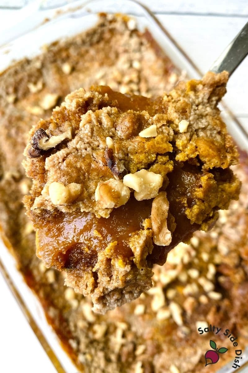 Pumpkin Pie Dump cake with spiced cake being scooped out with a bit of walnuts on top