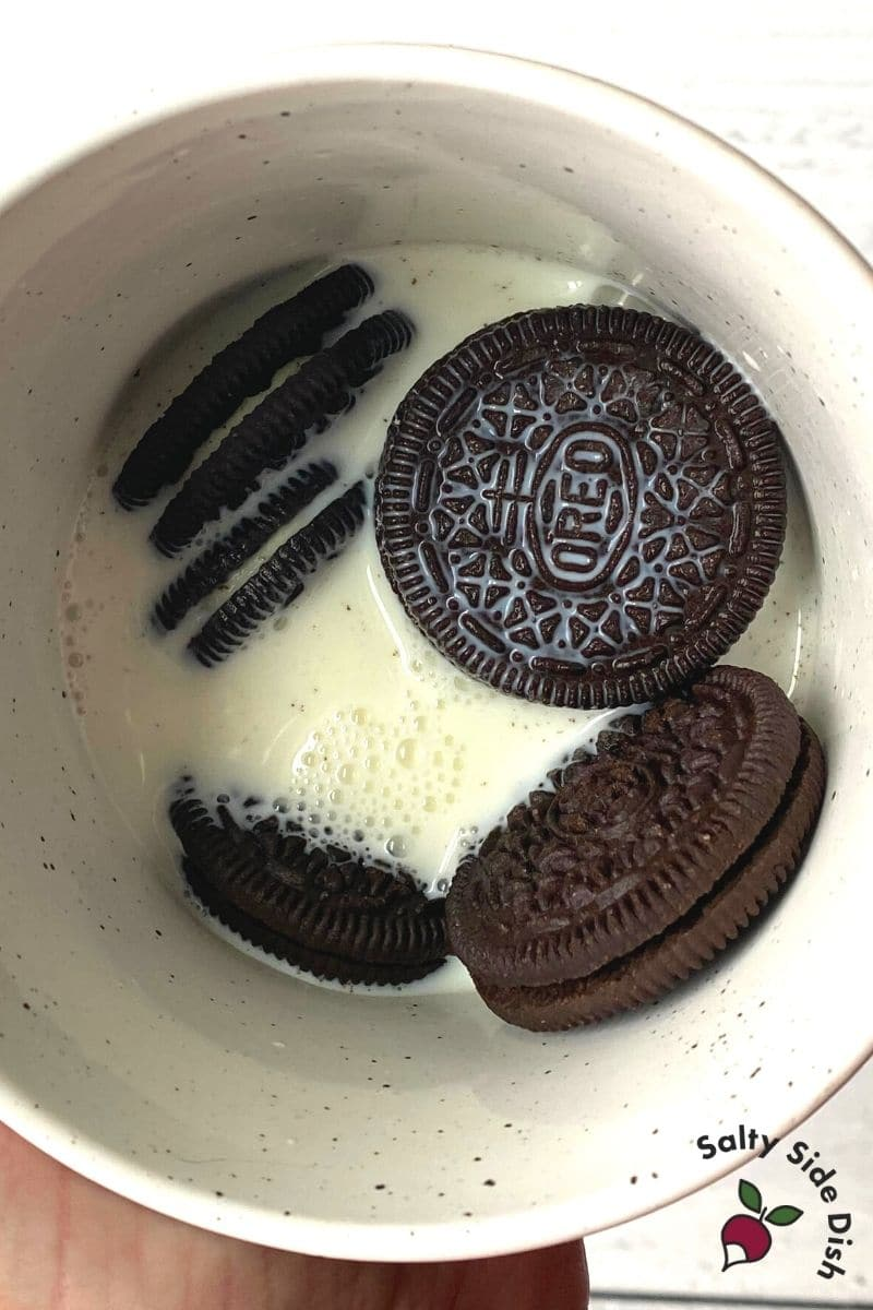 add oreos and milk to a coffee mug
