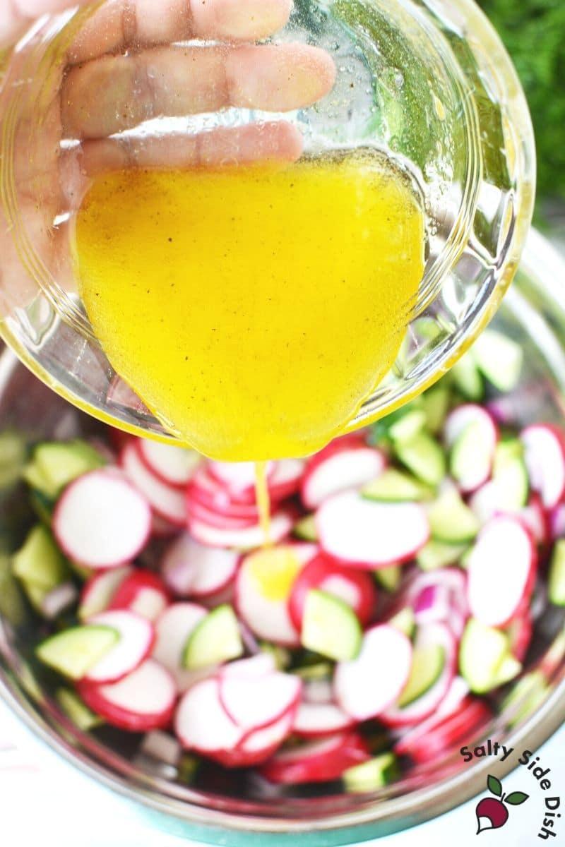 Pour marinade on cucumber and radish salad