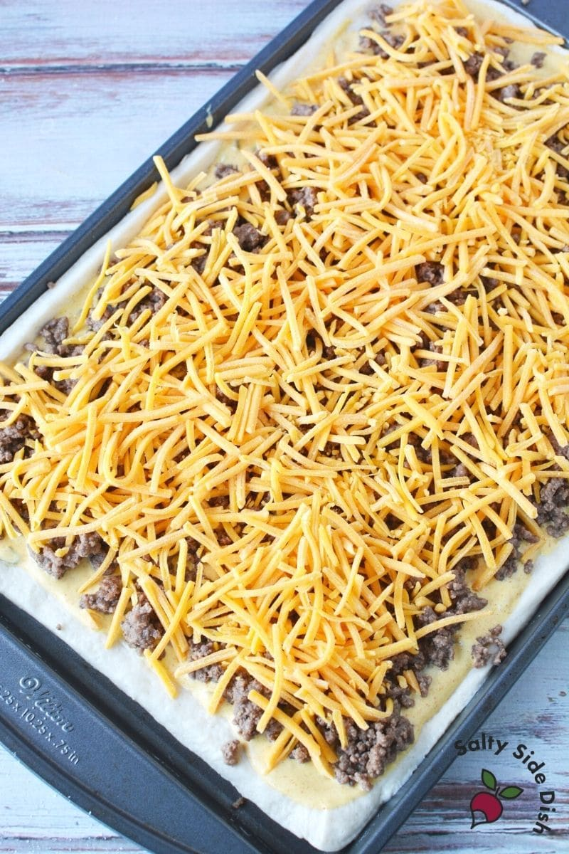 shredded cheese and ground beef baked on a pizza dough