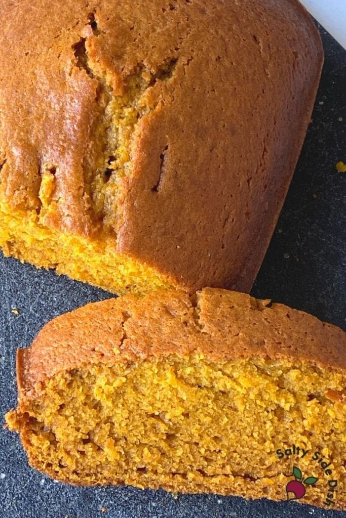 easiest pumpkin bread slice and leaning against larger pumpkin bread loaf