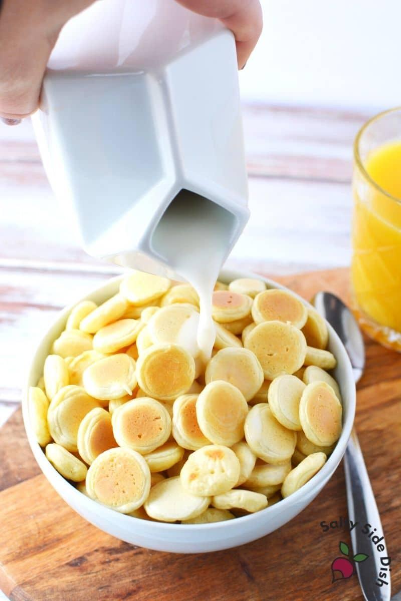 pouring milk over mini pancakes