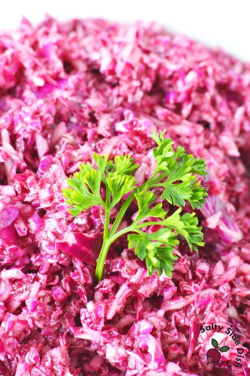 marinated cabbage salad shredded in a bowl with a piece of parsley