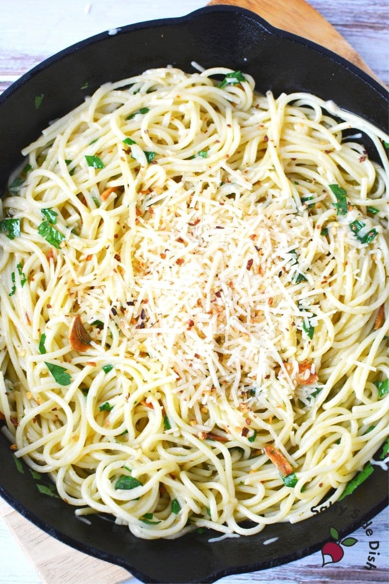 spaghetti aglio e olio with olive oil, garlic, cheese and red pepper flakes in a cast iron pan ready to serve with tongs