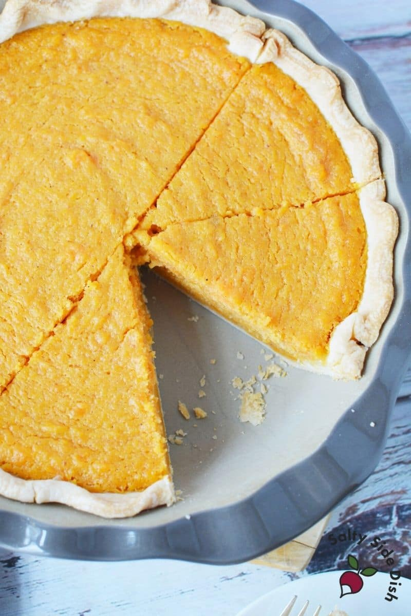 Baked sweet potato pie with crust and a slice taken out of pie