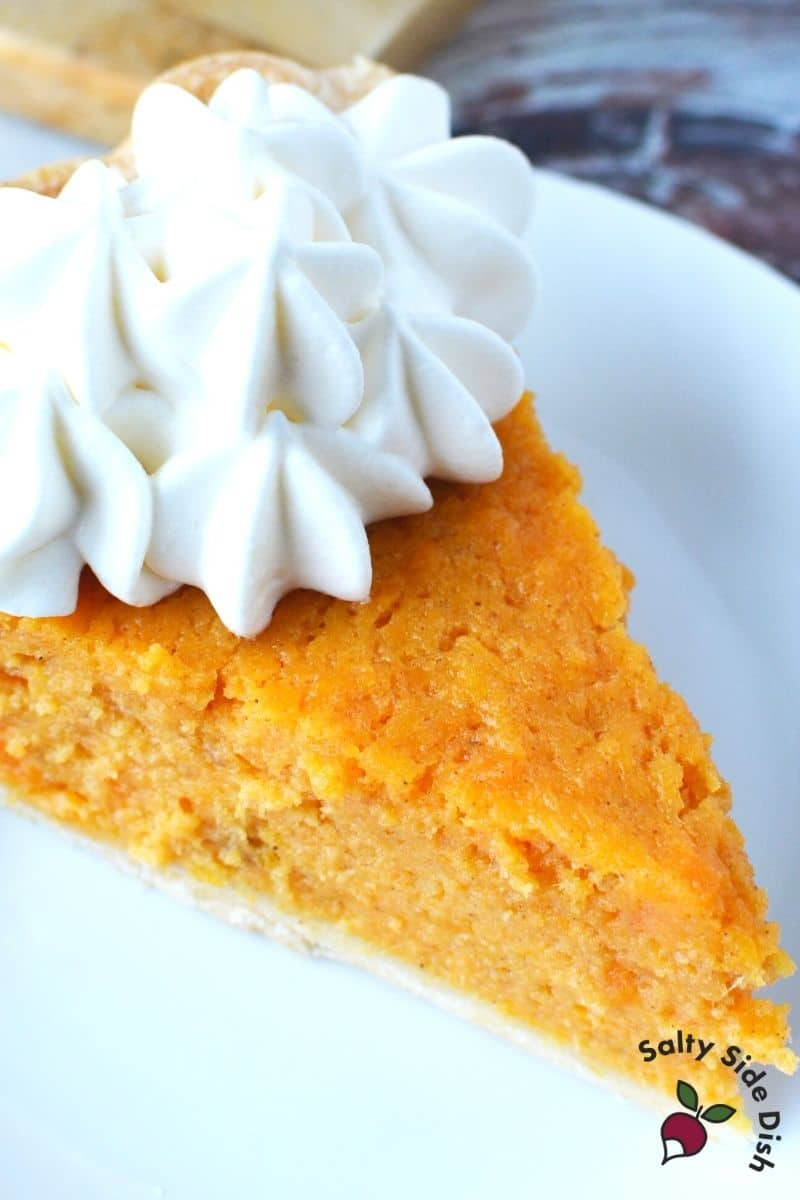 Southern sweet potato pie, sliced, with a dollop of whipped cream on top ready to serve