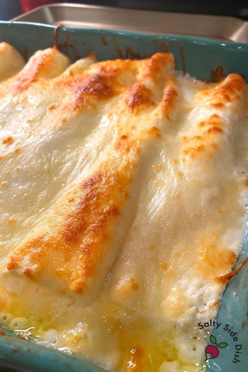 Cheesy White Chicken Enchiladas in a pan ready to serve