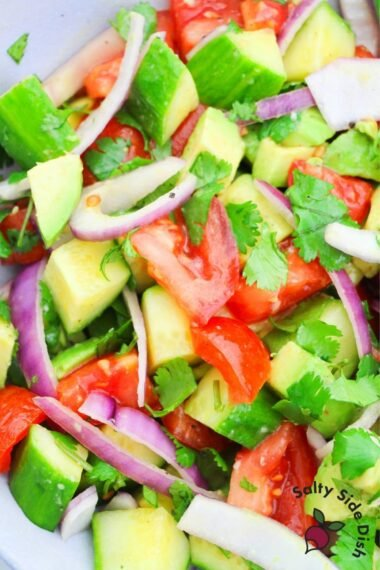 avocado salad recipe in a bowl with fresh cilantro and dressing