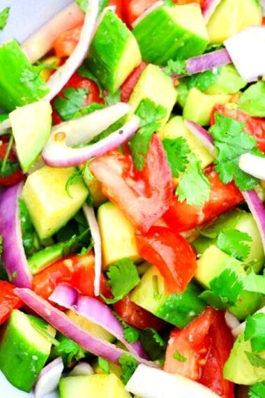 entire ingredients for avocado salad in a bowl with dressing added
